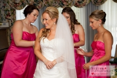 Bridesmaids help getting the brides dress on