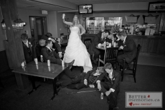 A funny set up photo of a bride standing strong while the groom and all the groomsmen are passed out