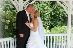 Weddding photo classic, of a bride and groom kissing in a beautiful gazebo on a golf course