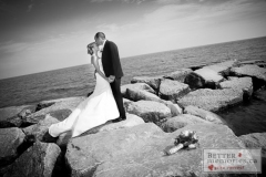 Bride and groom kissing on the rocks at Lakeview Park on Lake Ontario near the Jubilee Pavilion