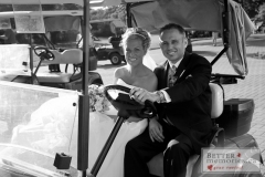 Groom driving a golf cart with his bride at the Oshawa Golf Club
