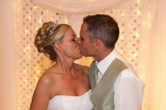 Bride and Groom kissing during the reception at the head table