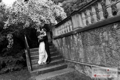Bride and Groom kissing on the steps by a stone wall