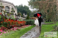 Bride and groom walking in the rain down a walkway with an umbrella