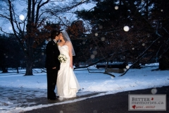 Bride and Groom outside kissing at nightfall while it snows