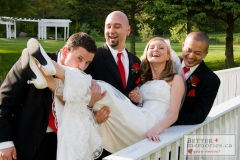 Groomsmen holding up the bride on the bridge at Trillium Trails