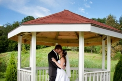 Bride and Groom Kissing in the Gazebo at Trillium Trails